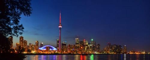 Photo de soir de Toronto où on voit, le long du lac, le paysage lumineux de la ville dont la Tour du CN.